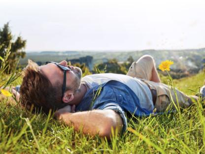 Mężczyzna swobodnie leży na trawie, górzysty krajobraz, obok pylący kwiat