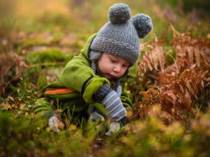 Małe dziecko w czapce i rękawiczkach bawi się jesienią w parku