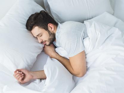 Młody mężczyzna z brodą śpi w białej pościeli