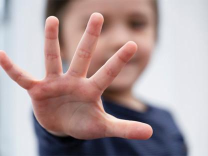 Dziecko pokazuje pięć palców u dłoni, liczy pięć wskazówek, jego twarz jest zamazana