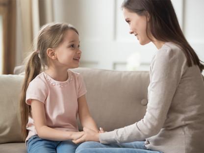 Uśmechnięte mama i córka na sofie rozmawiają o alergiach i Aleric spray do nosa
