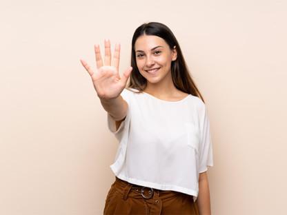 Młoda, uśmiechnięta brunetka wyciąga dłoń z pięcioma palcami, na których wylicza pięć wskazówek.