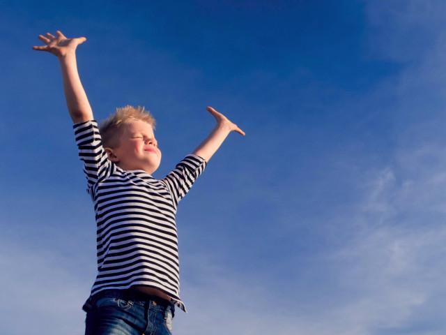 Mały chłopiec na tle nieba, rozkłada ręce i bierze głęboki oddech - Aleric spray