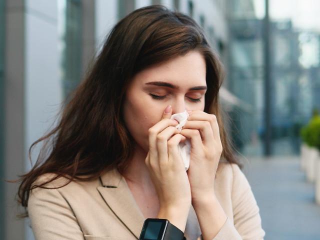 Młoda kobieta z alergią stoi w mieście i dmucha nos