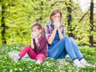 Mama i córka z alergią siedzą na trawie wśród stokrotek i dmuchają nos, Aleric spray do nosa na alergię