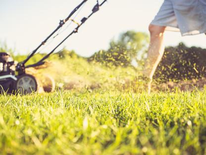 Kosiarka kosi trawę wiosną, prowadzi ją mężczyzna, widać go od pasa w dół, w powietrzu unosi się pył