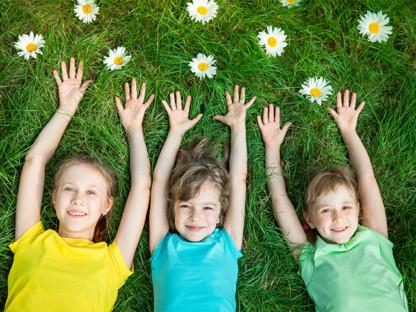 Trzy dziewczynki leżą na trawie wśród stokrotek z uniesionymi rękami i uśmiechami