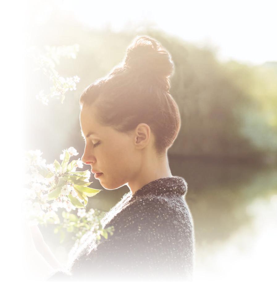 Młoda kobieta wącha kwiaty, cieszy się wiosną dzięki Aleric spray